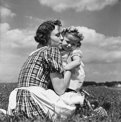 Mother kising her child in a field, c 1930s.
