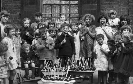 Children eating toffee apples, c 1930s.
