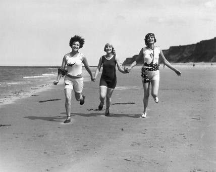 Women running along a beach, c 1920s.