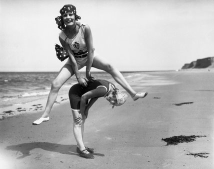 Two women in bathing costumes playing leapfrog on the beach, c 1920s.