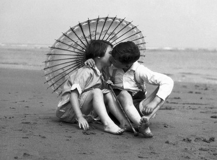 Girl and boy kissing under a parasol, c 1930s.