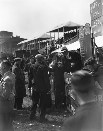 Bookmaker at a racetrack taking a bet from a gambler, c 1930s.