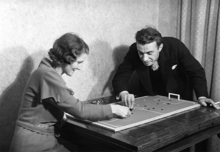 Couple playing tiddlywinks, c 1920s.