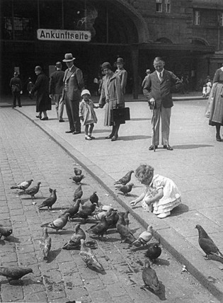 Little girl feeding pigeons in a German market square, c 1920s.