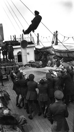 British officers tosing a colleague in a blanket on-board a ship, c 1910s.