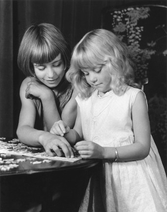 Two young girls doing a jigsaw, c 1930s.