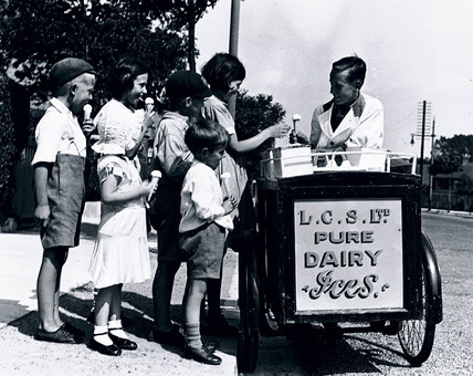 Children buying ice cream from a street vendor, c 1920s.