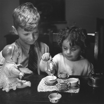 Young girl pouring tea as her brother looks on, c 1930s.