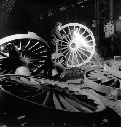 Burning the excess metal off the rough, unmachined, driving wheel, c 1958.