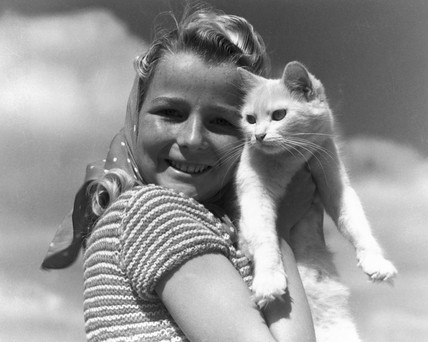 Girl posing for camera with a white cat, c