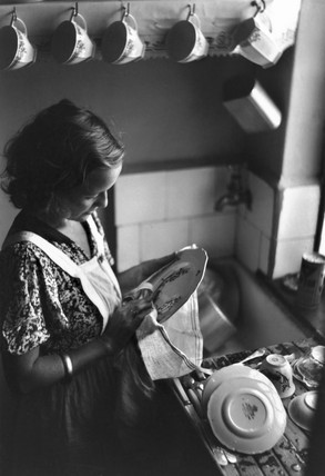 Young woman drying dishes, c 1930s.