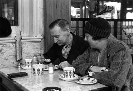 Couple enjoying a snack in a cafe, 1930s.