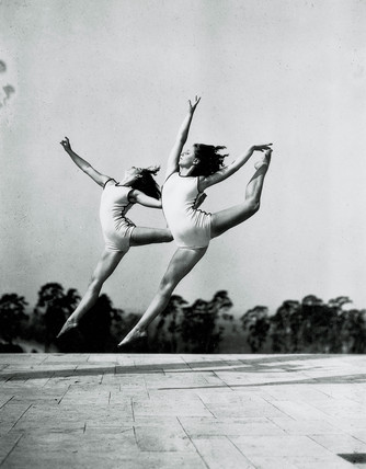 Two women gymnasts in mid-air, c 1930s.