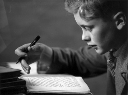 Schoolboy doing his homework, c 1930s.
