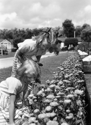 Two young girls smelling flowers, c 1930s.