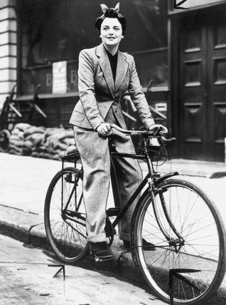 Young woman on a bicycle, wearing a trouser