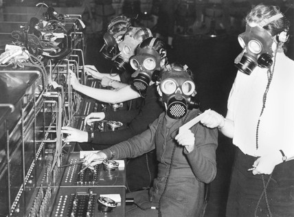 Telephone exchange operators in gas masks, 31 October 1938.
