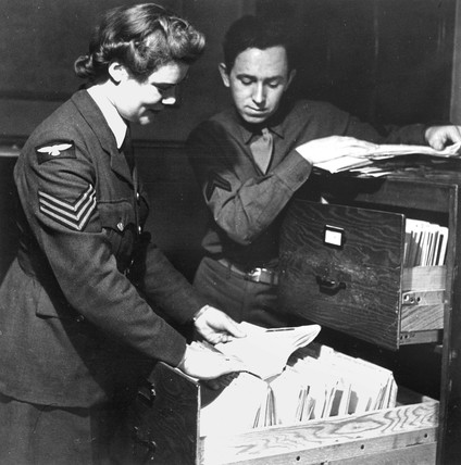 Military personnel looking through files, 1