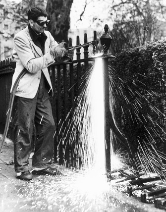 Workman dismantling railings, London, World War Two, 17 November 1941.