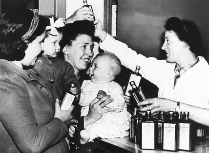 Mothers receiving American provisions, World War Two, 12 March 1942.