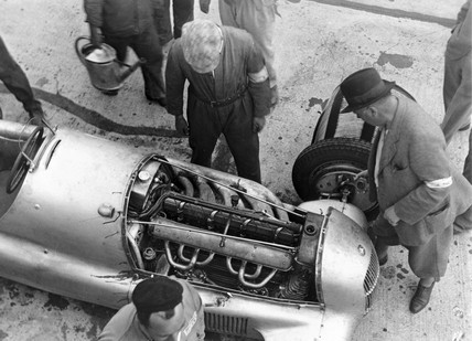 Looking at a Mercedes car engine, 1934.