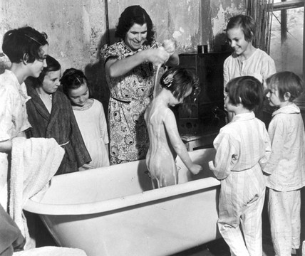 Young girl being washed in a bathtub, 1 Nov