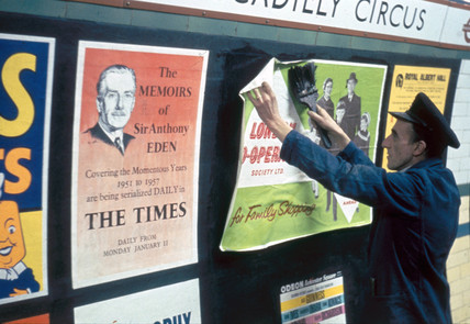Billposter at work, Piccadilly Circus underground station, London, 1960.