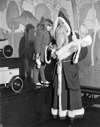 A little girl talking to Father Christmas, 23 December 1932.