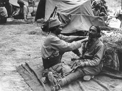 An Indian barber at work shaving his comrade, 1914-1918.