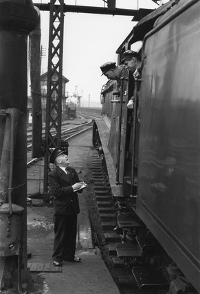 Driver and fireman consulting with station guard, c 1956.