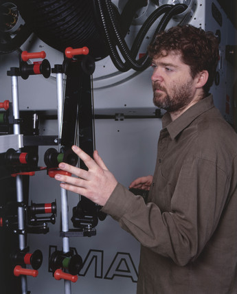 Technician lacing up a film onto an Imax projector, Science Museum, 2000.