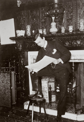C S Rolls standing by a fireplace reading, c 1900.