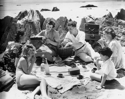 A family enjoying a picnic on a beach in th