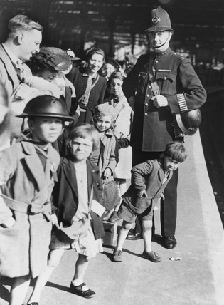 Evacuees with policeman on station platform, 28 September 1940.