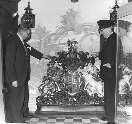 Two men inspecting Royal coat of arms, c 1965.