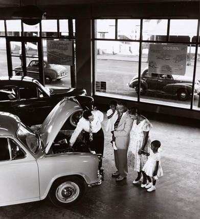 A Guyanian family are shown a Morris car in showroom, 1958.