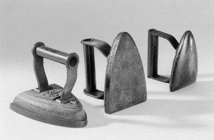 Two flat irons and one goffering iron, c 1850.