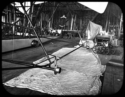 Outrigger wheels on Maxim's flying machine during assembly, 1894.