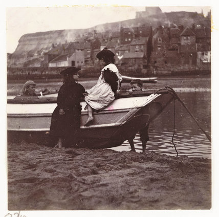 Children playing by the stern of a boat, Whitby Harbour, North Yorkshire, c 1905.