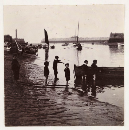 A group of boys playing by a boat, c 1905.