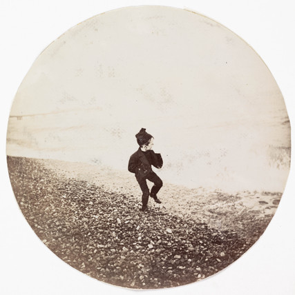 Boy running along the shoreline, c 1890.