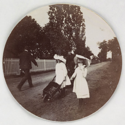 Children walking with a wheelbarrow, c 1890.