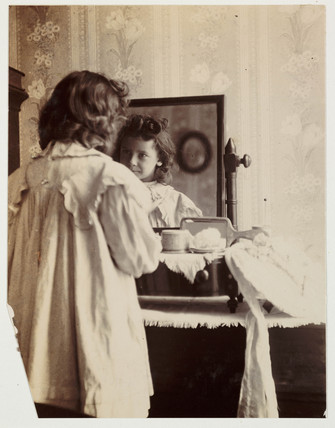 Girl looking into mirror, c 1890s.