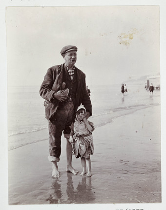 Man and small child paddling in the sea, c 1910.