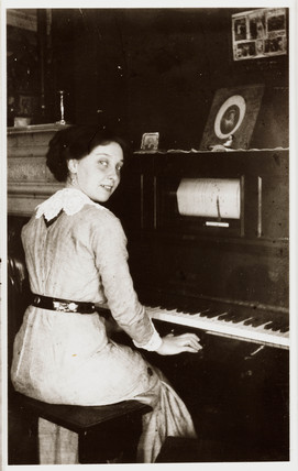 Woman sitting at a player-piano, c 1910.