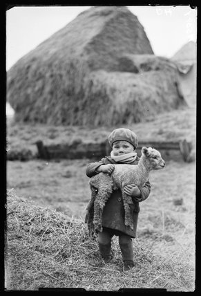 Little boy carrying a lamb, 1932.