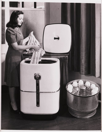 Woman using a Thor washer/dishwashing machine, 1947.