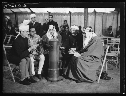 Muslim leaders warming themselves at a heater, Woking, 6 January 1935.