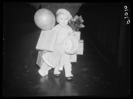 Small child with Christmas shopping, 1937.