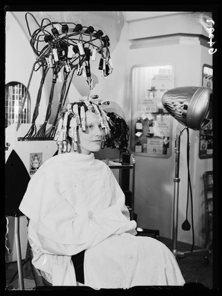 Woman sitting under a hair-curling machine, 1938.